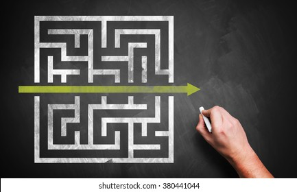 hand drawing a shortcut to a maze on a chalkboard