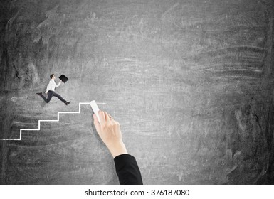 A hand drawing stairs with a chalk for a man with a folder running up. Black background. Concept of achieving your goal.