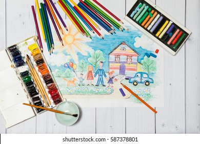 Hand drawn Bright Colorful Childrens Sketch With Happy Family, House, Dog, Car on the Lawn with Flowers with lying flat pencils, paints and pastel - concept of children creativity, close up top view