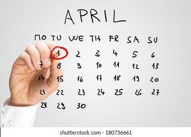 Hand drawn calendar for April on a virtual interface or screen with the First ringed in red by a man holding a marker pen, closeup of his hand. Fools day concept.
