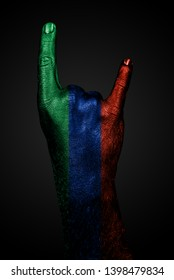 A hand with a drawn flag of Dagestan shows a goat sign on a dark background. Vertical frame