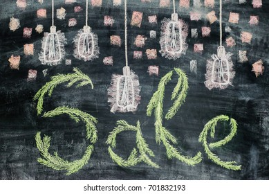hand drawn lettering of sale in chalk on black slate