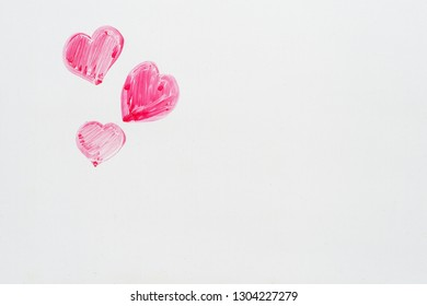 hand drawn pink Valentines Day hearts on the corner of a whiteboard with copyspace