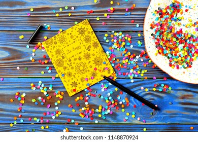 """Hand drawn yellow postcard with the inscription in doodle style """"Be happy"""" and plate with multi-colored confetti on blue wooden background. Top view"""