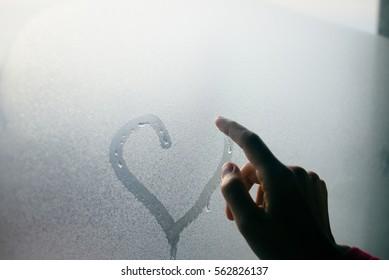 Hand draws love heart on cold fogged window background, closeup image