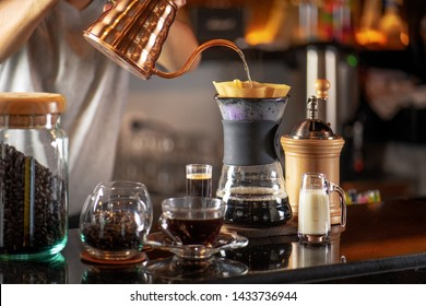Hand drip coffee, Barista making drip coffee by pouring spills hot water on coffee ground with prepare filter from copper  teapot to glass transparent chrome drip maker. on wooden table cafe shop