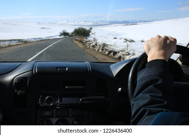 hand of driver behind the wheel of the right-hand drive car. winter landscape