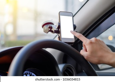 Hand of driver using smartphone which holding on magnet phone mount holder at the car windshield with screen for map GPS navigation on the traffic road background