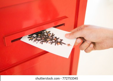 Hand dropping Christmas postcard into red mailbox sending Xmas wish to other people on seasonal holidays