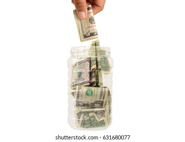 Hand Dropping Five Dollar Bill into Container full of US Currency Money isolated on white background