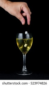 A hand dropping pills into a glass of wine, on a black background. There are two pills being dropped, one is in the wine, the other is still falling.