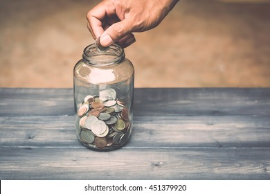 hand drops money into a glass jar for a savings