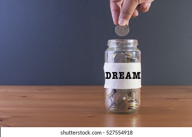 Hand drops money into a glass jar with DREAM label. Future and finance concepts.