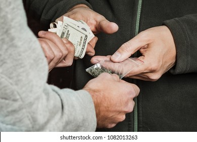 Hand drug addict with money buys a dose of marijuana from a drug dealer. Concept of drug abuse and trafficking.
