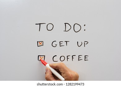 a hand with a dry erase marker checking off a to do list with get up and coffee on a whiteboard