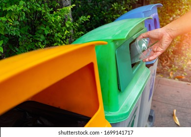 Hand dump plastic bottle in colorful bins are separate the garbage before leaving in the trash recycling container ecology.Color separation bin according to waste type.