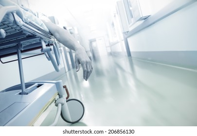 Hand of a dying patient lying on a mobile bed in hospital corridor
