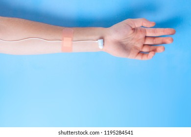 Hand with earphones like medical IV infusion on a blue background. Music addiction. Music concept. Copy space