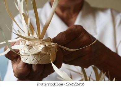 The hand of an elderly Asian woman weaving a container from the dried palm leaves.