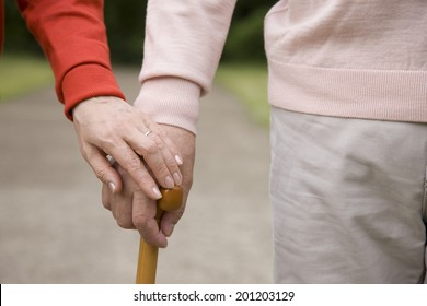 The hand of the elderly couple overlapping their hands each other to the cane