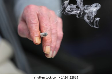 The hand of an elderly person, holding a lit up cigarette. The nails of his index finger and ring finger are completely turned yellow because of the tar, nicotine and smoke. Concept of chain smoker.