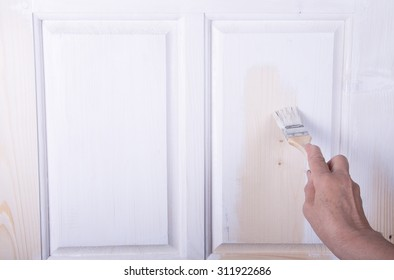 Hand of an elderly woman with a paint brush with white paint door. Selected focus