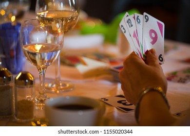 hand of an elderly woman with playing cards held as a fan next to a table with drinks in a bar