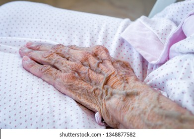 Hand of an elderly woman's hand wearing pajamas. Aging process.