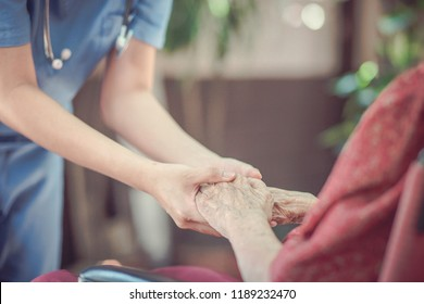 Hand of  eldery  woman with her caregiver at home. Home care or Elderly care concept.