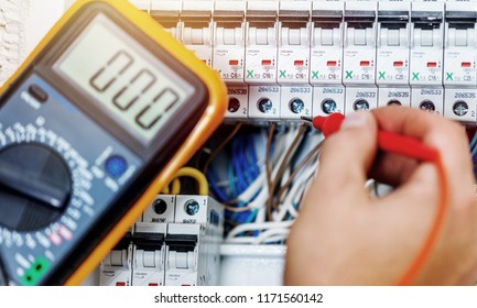 Hand of an electrician with multimeter probe at an electrical