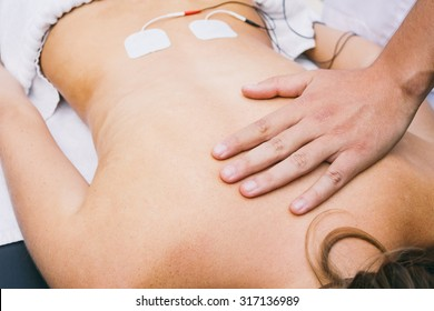 Hand and electrodes on a patient's lumbar
