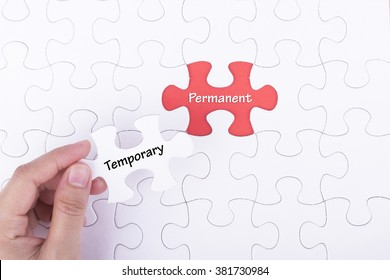 Hand embed missing a piece of puzzle into place, red space with word TEMPORARY PERMANENT. Business and financial concept.