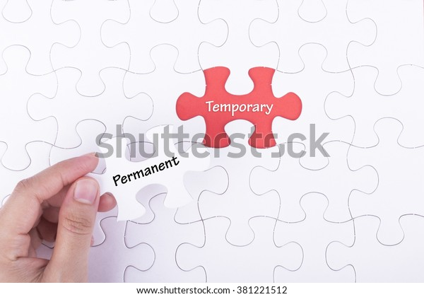 Hand embed missing a piece of puzzle into place, red space with word PERMANENT TEMPORARY. Business and financial concept.
