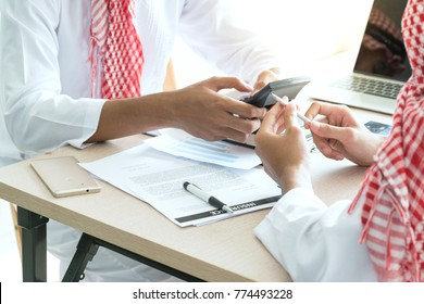 Hand of Emirati Arab friends  talking together with document on table