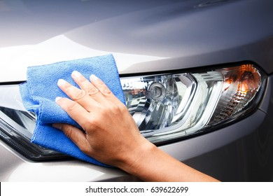 Hand of employees worker use clean blue cloth to wipe the car after washing in the car wash shop