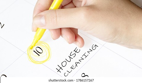hand encircles a date on a calendar with text House Cleaning yellow felt-tip pen