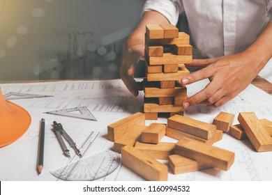 Hand of engineer playing a blocks wood tower game (jenga) warm colours sun light