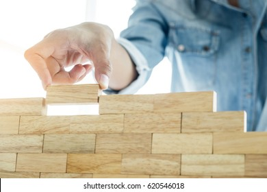 Hand of engineer playing a blocks wood tower game (jenga) on blueprint or architectural project concept
