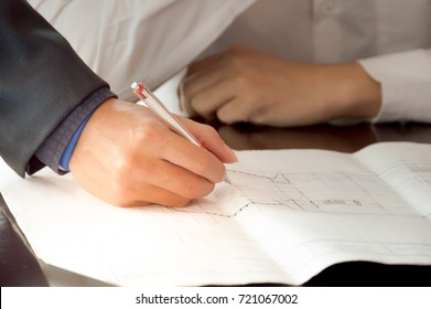 Hand engineer writing blueprint paper on table at workplace