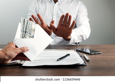 Hand with envelope and US dollars. The entrepreneur, refuses the envelope as a bribe. The concept against corruption in business activities, against bribery.