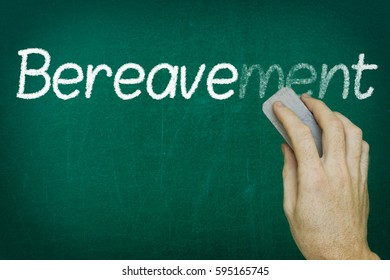 Hand erasing the word BEREAVEMENT written on blackboard