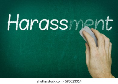 Hand erasing the word HARASSMENT written on blackboard