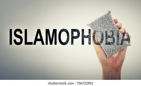 Hand erasing the word ISLAMOPHOBIA. Conceptual poster for rejecting islamophobia and racism.