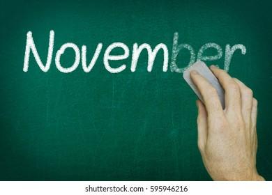 Hand erasing the word NOVEMBER written on blackboard