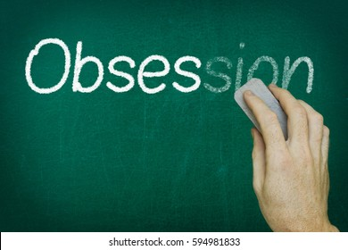 Hand erasing the word OBSESSION written on blackboard