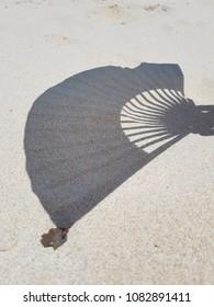 Hand fan shadow on the sandy beach