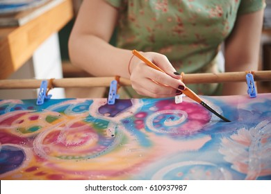 Hand of female artist painting on fabric