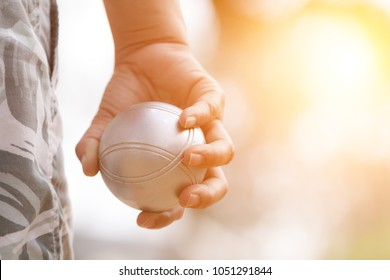 Hand of female boule holding boule or petanque ball on match