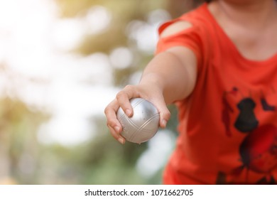 Hand of female boule holding boule or petanque ball and bag to prepare for a match