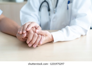 Hand of female doctor holding on her senior patient - selective focus point